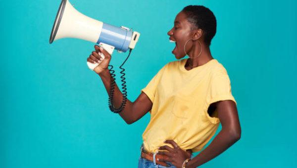 Mulher negra, feliz, falando no autofalante